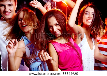 Portrait of glad teens looking at camera with smiles during disco
