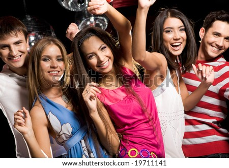 Portrait of glad teens looking at camera with smiles during party