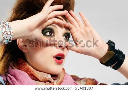 portrait of glam punk redhead girl looking through her hands like binocular - stock photo