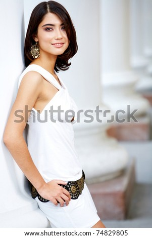 Portrait of glamorous girl with brown hair standing near column