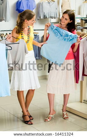 Portrait of glamorous girls holding tanktops in hands while choosing new clothes in the trade center - stock photo