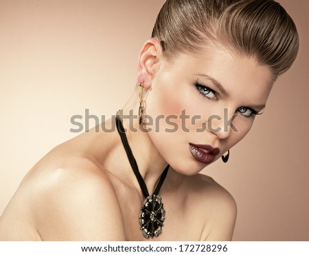 Portrait of glamour girl with professional make-up and hairdress wearing black shiny necklace and golden earrings.  - stock photo