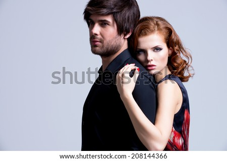 Portrait of glamour sexy couple in love posing at studio in elegance clothes. - stock photo
