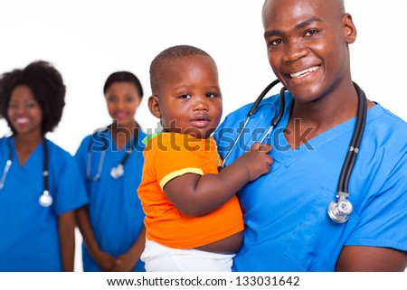 portrait of good looking african american male pediatric doctor with little boy and female nurses on background - stock photo