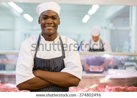 portrait of good looking afro american butcher arms folded - stock photo