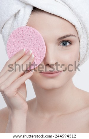 Portrait of good-looking blue-eyed young lady with natural make-up, french manicure and clear skin with white towel on her head and pink rough sponge in her left hand closing her left eye. - stock photo