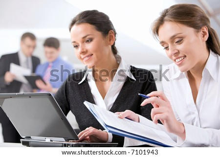 Portrait of good-looking business women working on the background of men