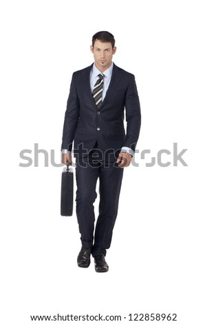 Portrait of good looking businessman holding briefcase while walking on a white surface - stock photo