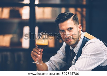 Portrait of good-looking man with wine glass full of aromatic coffee