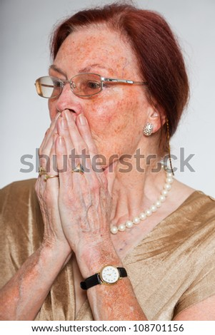 Portrait of good looking senior woman wearing glasses with expressive face showing emotions. Scared and frightened. Acting young. Studio shot isolated on grey background.