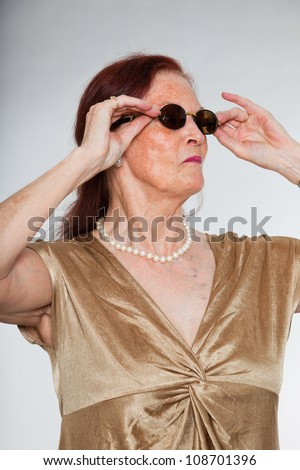 Portrait of good looking senior woman wearing sunglasses with expressive face showing emotions. Acting young. Studio shot isolated on grey background.