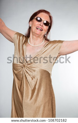 Portrait of good looking senior woman wearing sunglasses with expressive face showing emotions. Happy and free. Acting young. Studio shot isolated on grey background. - stock photo
