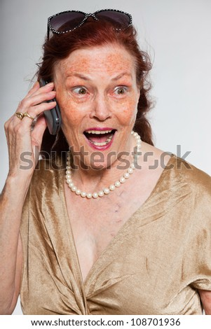Portrait of good looking senior woman with expressive face showing emotions. Calling with cell phone. Acting young. Studio shot isolated on grey background. - stock photo