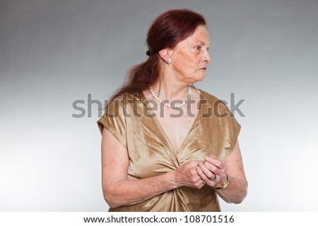 Portrait of good looking senior woman with expressive face showing emotions. Pensive and serious. Acting young. Studio shot isolated on grey background.