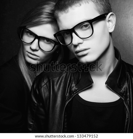 Portrait of gorgeous fashion twins in black clothes wearing trendy glasses and posing over gray background together. Hipster style. Black and white (monochrome) studio shot. - stock photo