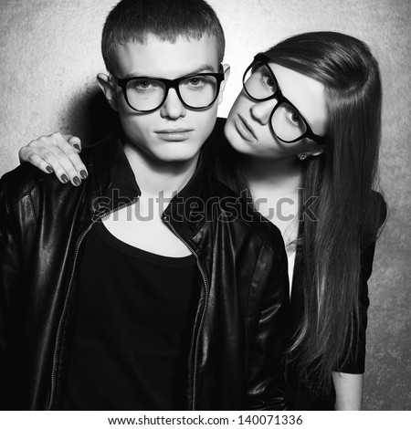 Portrait of gorgeous fashion twins in black clothes wearing trendy glasses and posing over metal background together. Perfect hair and skin. Natural make-up. Black and white studio shot