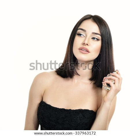 Portrait of gorgeous lady with perfume, young beautiful woman holding bottle of perfume and smelling aroma over white background - stock photo