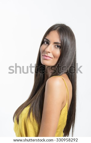 Portrait of gorgeous Latino woman with long straight hair looking at camera over gray studio background.