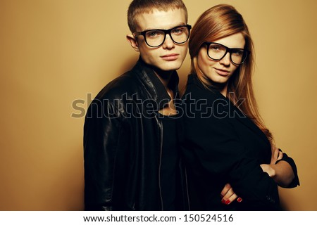 Portrait of gorgeous red-haired fashion twins in black clothes wearing trendy glasses and posing over beige background together. Perfect hair. Natural make-up. Perfect skin. Studio shot - stock photo