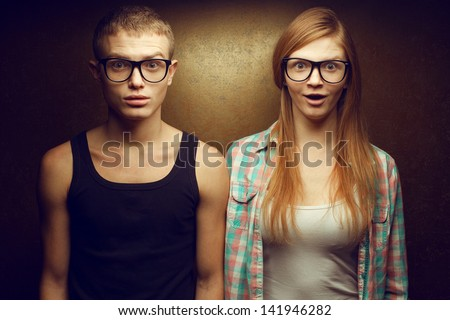Portrait of gorgeous red-haired (ginger) fashion twins in casual shirts wearing trendy glasses and posing over golden background together with wow faces (duck-face). Hipster style. Studio shot - stock photo