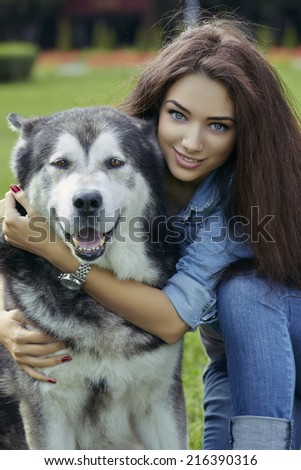 Portrait of gorgeous smiling young lady with blue eyes, long hair and wearing blue jeans hugging a big Alaskan Malamute male dog while looking at the camera. - stock photo