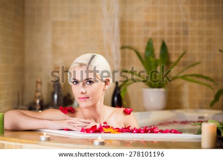 Portrait of gorgeous woman in jacuzzi with rose petals - stock photo