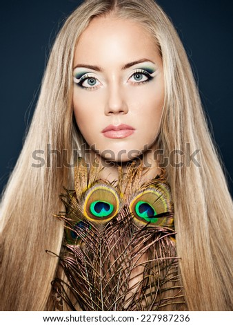Portrait of gorgeous woman model with evening creative makeup and shiny straight long hair decorated peacock, feather.  - stock photo