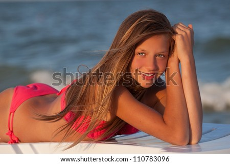Portrait of gorgeous young girl  smiling while looking at you on the beach - stock photo