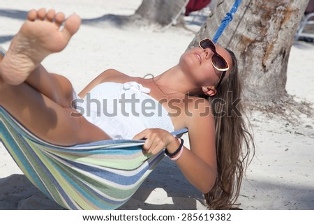 Portrait of gorgeous young woman in sleeping in a hammock on a tropical island. Travel holidays concept. - stock photo