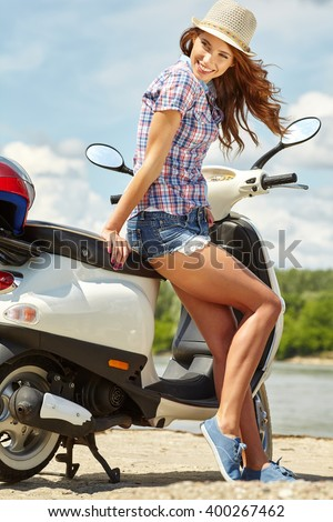 Portrait of gorgeous young woman on scooter