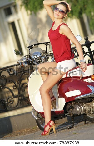 Portrait of gorgeous young woman on scooter - Outdoor on street - stock photo