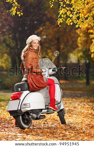 Portrait of gorgeous young woman on scooter posing in the park
