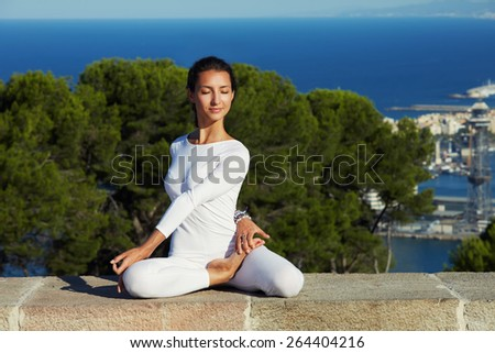 Portrait of gorgeous young woman practicing yoga on a sunny day with amazing sea view from high altitude, woman seeking enlightenment through meditation, relaxed girl performing yoga routine - stock photo