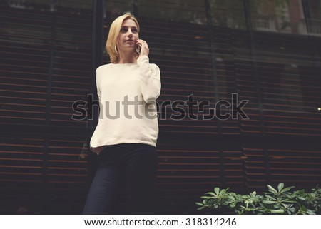 Portrait of gorgeous young woman talk on smart phone standing outdoors in the city on blank copy space area for text message or information, female hipster at mobile phone conversation, filter image - stock photo