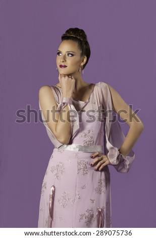 Portrait of gorgeous young woman wearing pink and silver dress with spring makeup, standing with her hand to her chin while she is lost in thought. - stock photo