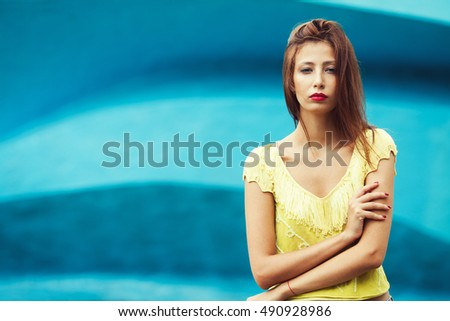 Portrait of gorgeous young woman wearing trendy yellow-green handmade knitted top, posing over construction symbolizing ocean. Urban style. Close up. Outdoor shot