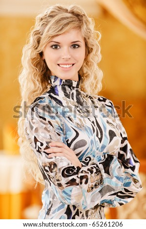 Portrait of graceful charming smiling young with crossed hands woman against golden magnificent interior.