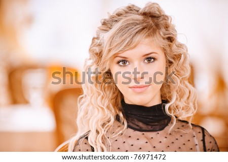 Portrait of graceful charming smiling young woman against golden magnificent interior.