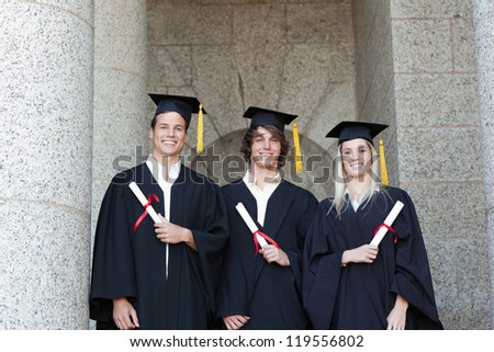 Portrait of graduates holding their diploma with university in backgroung