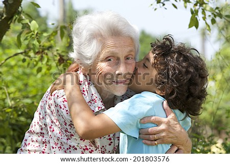 Portrait of grand son embracing  happy grandmother  with tenderness in the  garden  - stock photo