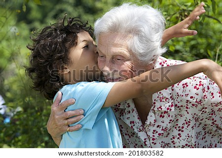 Portrait of grand son hugging and embracing  happy grandmother in the  garden  - stock photo