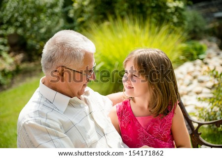 Portrait of grandchild with grandfather - outdoor in backyard - stock photo