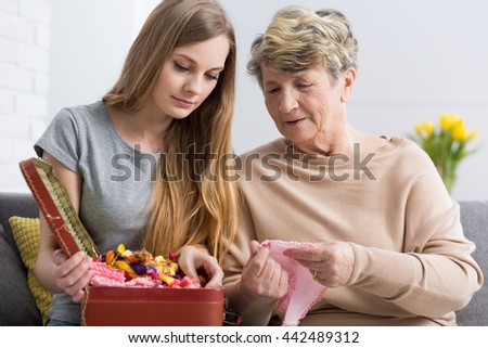 Portrait of granddaughter and grandmother opening a casket full of decorative materials for handcraft