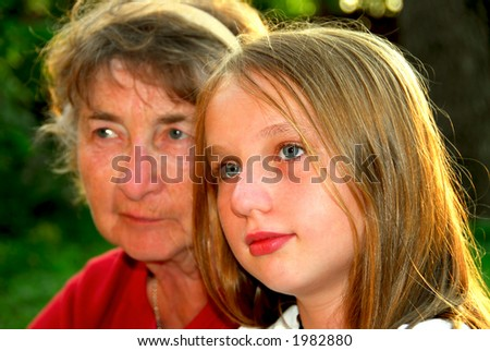 Portrait of grandmother and granddaughter in summer park, focus on the girl - stock photo