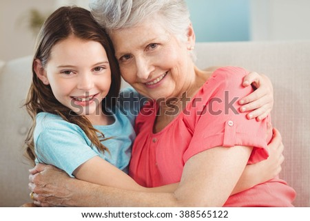 Portrait of grandmother and granddaughter smiling while embracing each other - stock photo