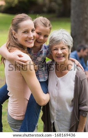 Portrait of grandmother, mother and daughter standing at the park - stock photo