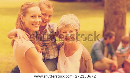 Portrait of grandmother mother and daughter with family in background at the park - stock photo