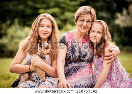 Portrait of grandmother with grandchildren and dog - outdoor in nature