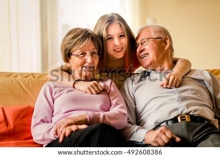 Portrait of grandparents with their teenage granddaughter sitting on sofa at home