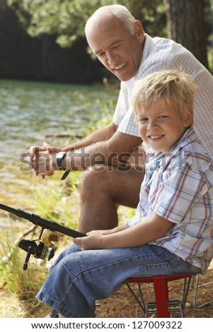 Portrait of grandson holding fishing rod with grandfather sitting in the background
